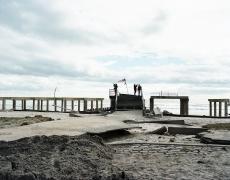 "Susannah Ray<br /> <em>Flag Over Boardwalk Remnants, Rockaway Beach, NY, October</em>, 2012<br /> Digital C-prints<br /> 24 x 30""  Edition of 10<br /> 40 x 50""  Edition of 5"